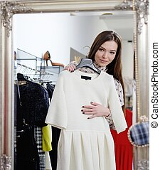 Young woman choosing clothes in a showroom