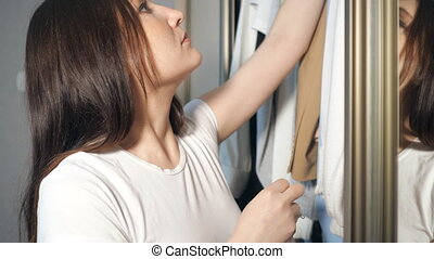 Young woman choosing clothes in wardrobe at home, 4k