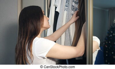 Young woman choosing clothes in wardrobe at home.