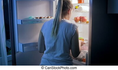 Young woman choosing healthy food. Girl opens refrigerator...