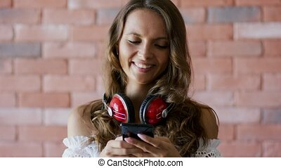 Young woman choosing music on smartphone - Beautiful young...