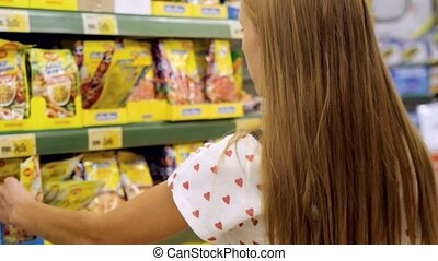 Young woman choosing spices in grocery store.