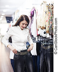 Young woman choosing trousers at market