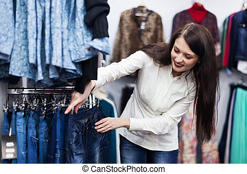 Young woman choosing trousers at boutique