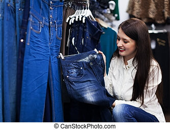 Young woman choosing trousers at shop