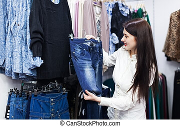 Young woman choosing trousers at store