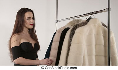 Young woman choosing winter fur coat in front of clothing rack
