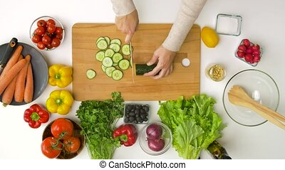 young woman chopping cucumber at home - healthy eating, ...