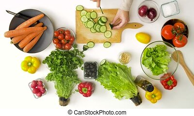 young woman chopping cucumber for salad at home - healthy ...