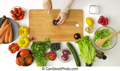 young woman chopping red onion at home - healthy eating, ...