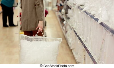 young woman chose a pillow in a supermarket