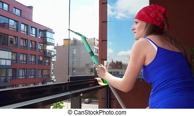 young woman cleaning glass window with special tool at home balcony