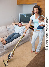 Young woman cleaning house while carrying baby