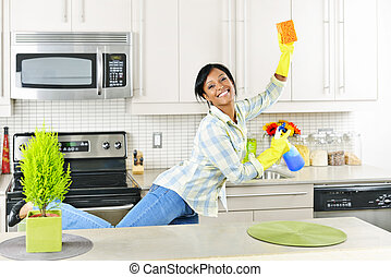 Young woman cleaning kitchen