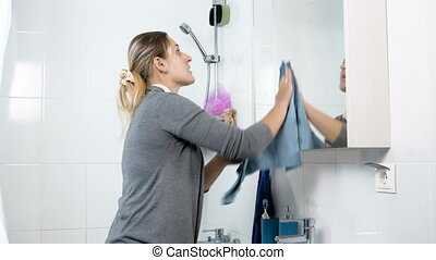 Young woman cleaning mirror in bathroom with blue cloth
