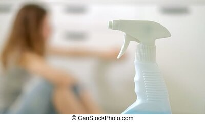 young woman cleaning with duster at kitchen at home