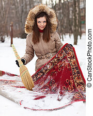 woman cleans red carpet with snow