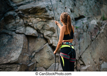 Young Woman Climber Belayer Holding the Rope near the Rock in the Mountains. Adventure and Extreme Sport Concept