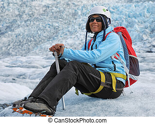 Young woman climber resting on top of a glacier