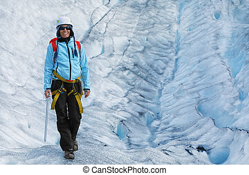Young woman climber standing in the cleft of the glacier