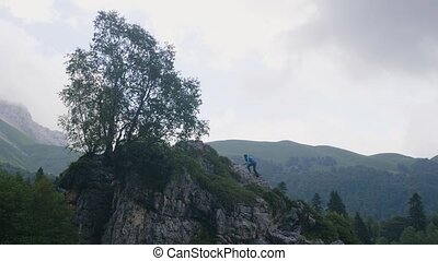 Young woman climbing on top of mountains and enjoying nature landscape