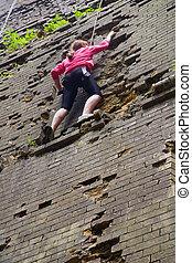 Young woman climbing up brick wall