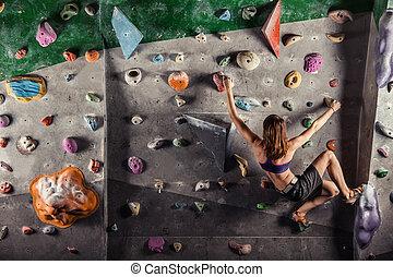 Young woman climbing up on practice wall