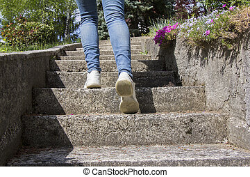 Young woman climbs on concrete stairs
