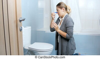 Young woman closes her nose with clothesping before cleaning...