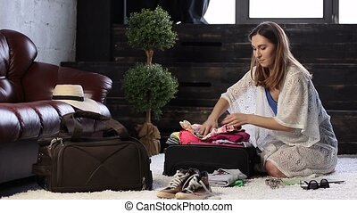 Young woman closing suitcase full of clothes