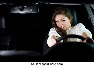 young woman clutching a steering wheel anticipating a collision. copy space