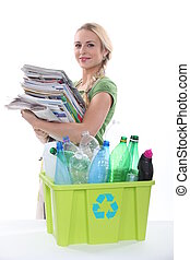 young woman collecting paper and plastic for recycling