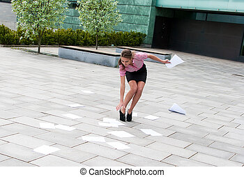 Young woman collecting papers from the asphalt