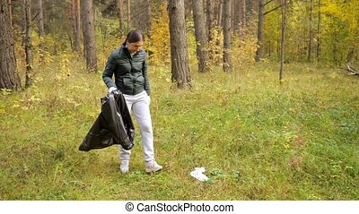 Young woman collecting trash in the forest.