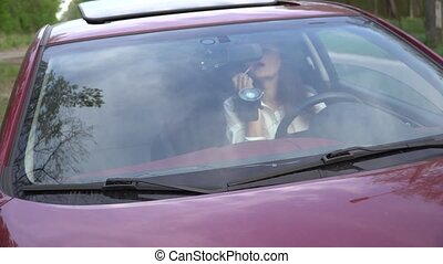 Young woman color her lips with rouge while sitting in car