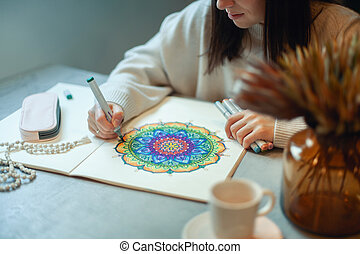 Young woman colouring mandala with markers and white rosary on table with cup of coffee at home