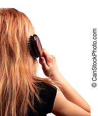 Young woman combing her hair