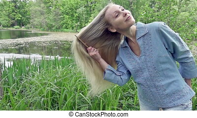 young woman combs a long fair hair on the bank of the lake...