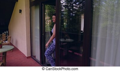 Young woman coming on terrace to relax in the morning - Pan...
