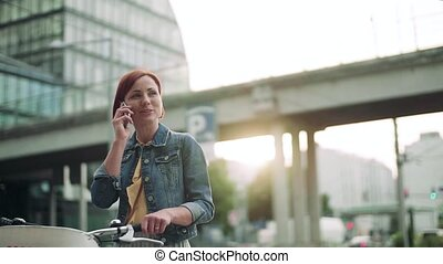 Young woman commuter with smartphone and bicycle standing outdoors in city.