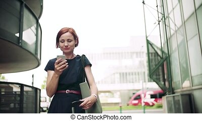 Young woman commuter with smartphone standing outdoors in ...