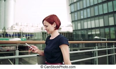 Young woman commuter with smartphone walking on bridge ...