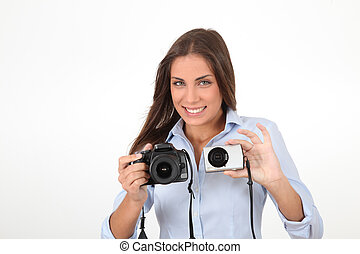 Young woman comparing digital compact and reflex cameras