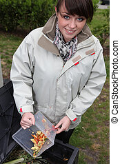 Young woman composting vegetables