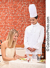 young woman congratulating female chef in restaurant
