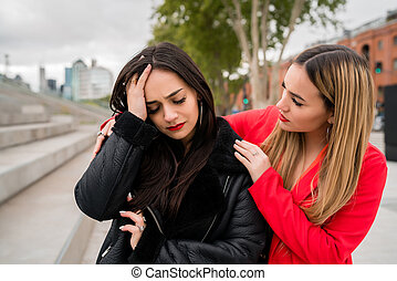 Young woman consoling and comforting her upset friend.