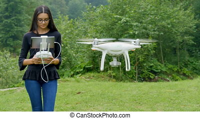 Young woman controlling drone with a transmitter remote...