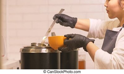 Young woman cook pouring hot soup from saucepan into bowl...