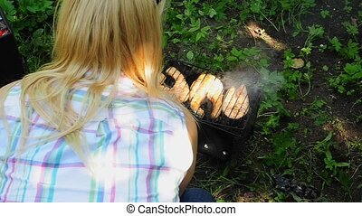Young woman cooking fish on grill