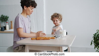 Young woman cooking pastry with small child in kitchen in apartment